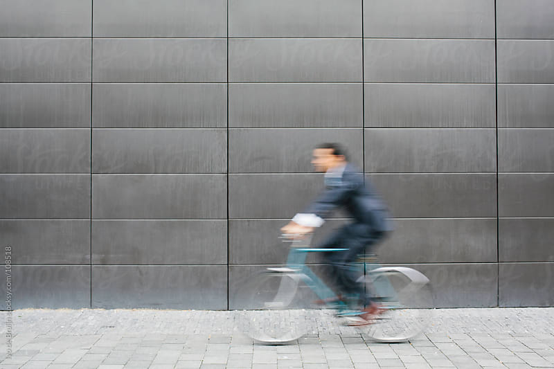 Unsharp, blurry image of a business man on his bike by Ivo de Bruijn for Stocksy United