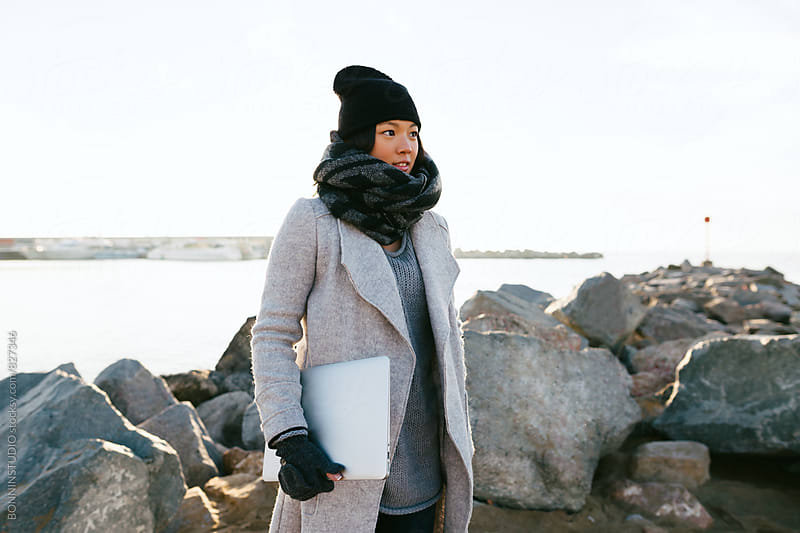 Woman wearing winter clothes holding a laptop on a breakwater. by BONNINSTUDIO for Stocksy United