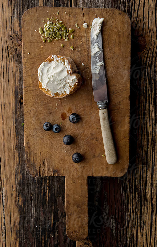 Making Crostini with Goat Cheese and Blueberry on Cutting Board by Studio Six for Stocksy United