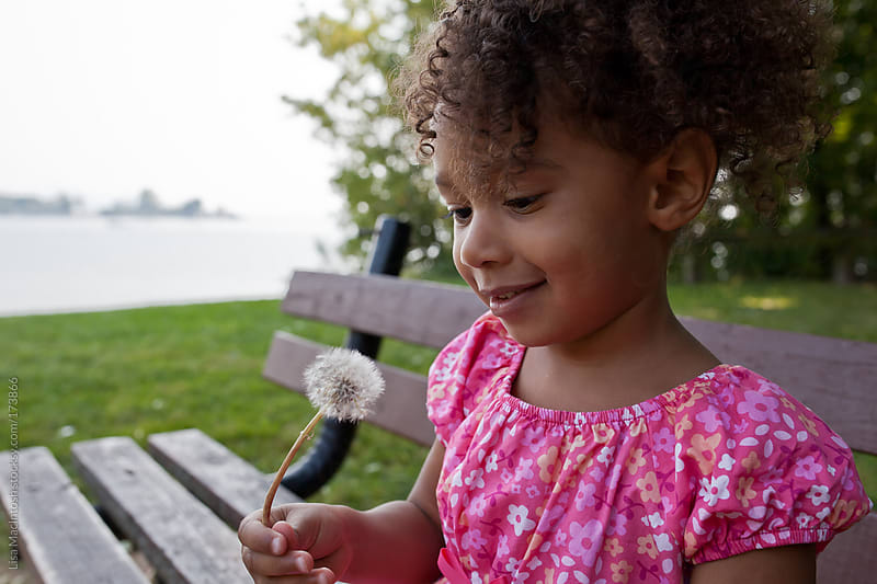 young black girl wearing pink dress, smiling down at dandelion by Lisa MacIntosh for Stocksy United