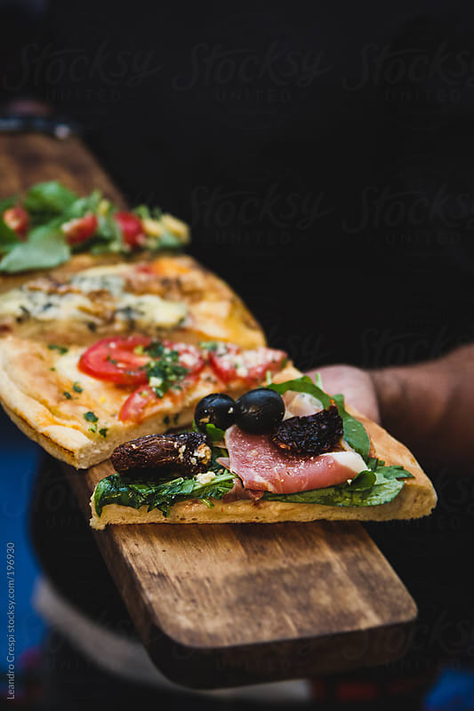 Pizza portions over wood for serve by Leandro Crespi for Stocksy United
