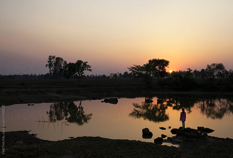 A girl standing in front of a waterbody and enjoying sunset by PARTHA PAL for Stocksy United