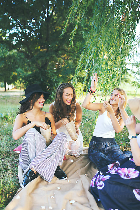 Group of happy female friends throwing popcorn at each other by Jovana Rikalo for Stocksy United
