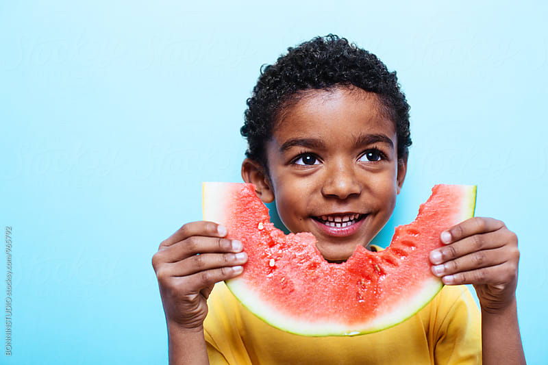 Little boy eating a fresh watermelon on blue wall. by BONNINSTUDIO for Stocksy United