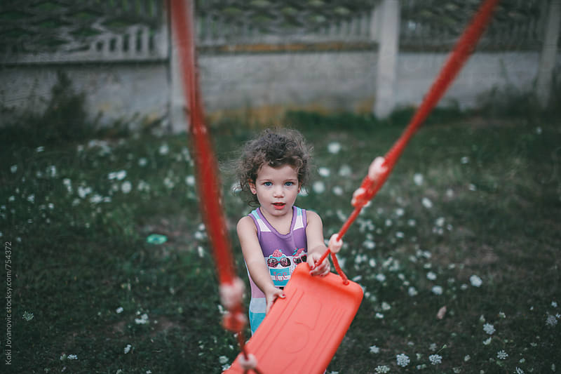 young girl playing in the backyard by Koki Jovanovic for Stocksy United
