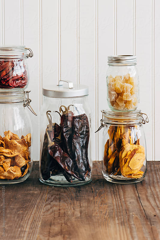 Five jars on a wood counter containing dehydrated fruits and vegetables. by Lucas Saugen for Stocksy United
