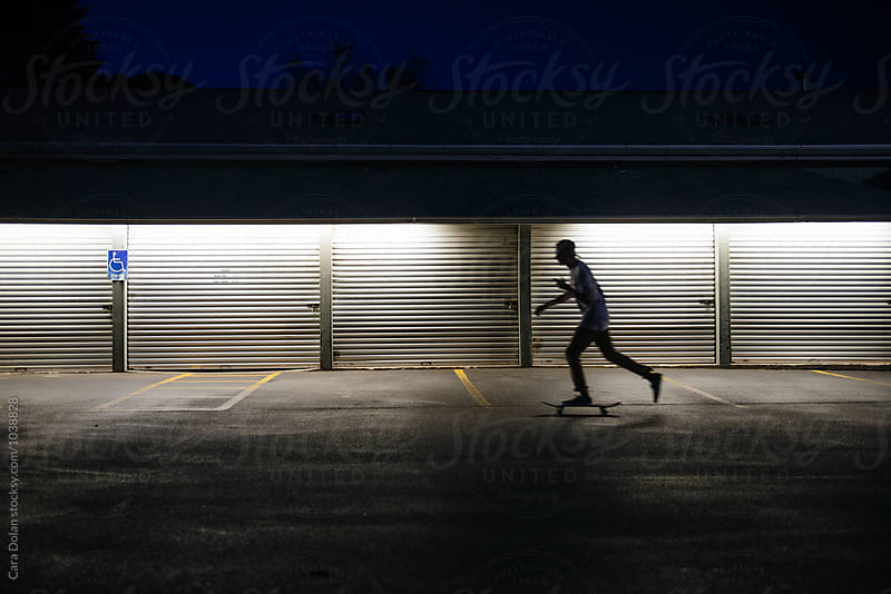 Skateboarder in a parking lot at night by Cara Dolan for Stocksy United