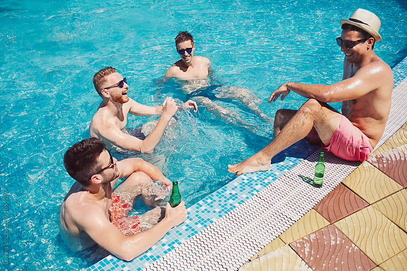 Men Enyouing Beer by the Pool by Lumina for Stocksy United