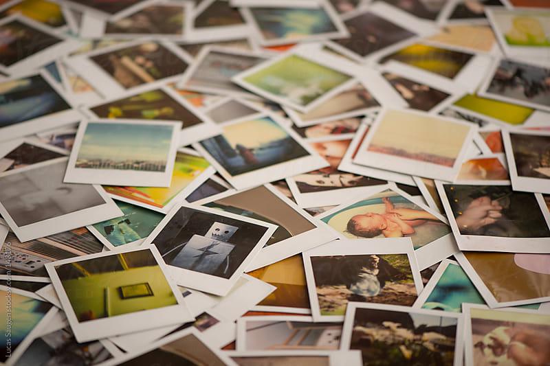 Table covered in polaroid photos. by Lucas Saugen for Stocksy United