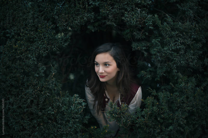 Woman Peeking Out of a Bush by Lumina for Stocksy United