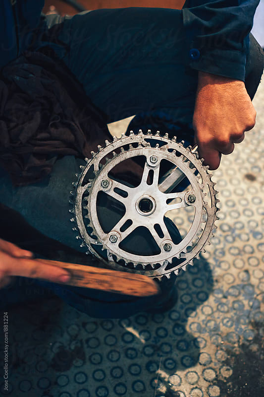 Man brushing a chain wheel. by Jose Coello for Stocksy United