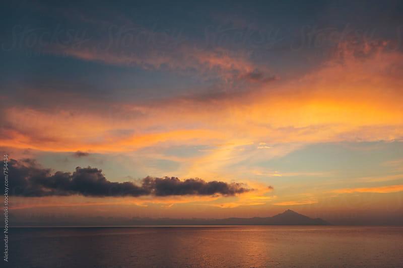 Minimalist seascape with dramatic sky and clouds above Athos, Greece by Aleksandar Novoselski for Stocksy United
