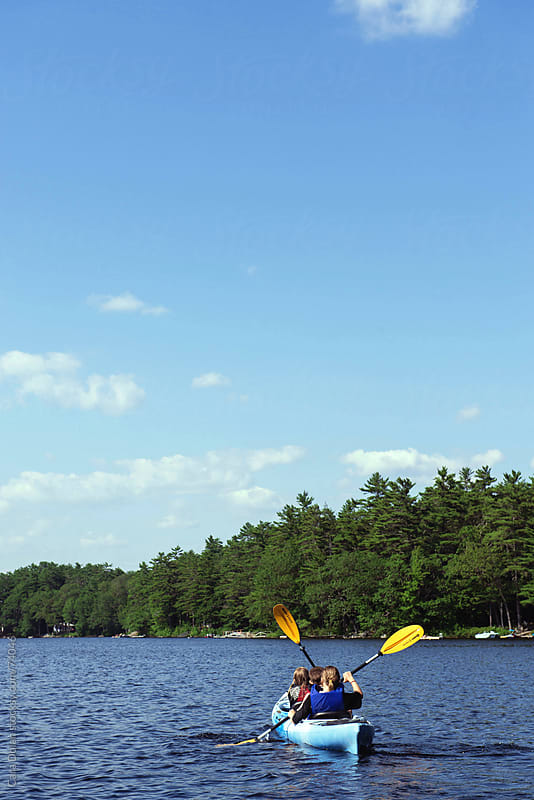 Kids kayak together on a lake on a beautiful summer day by Cara Slifka for Stocksy United