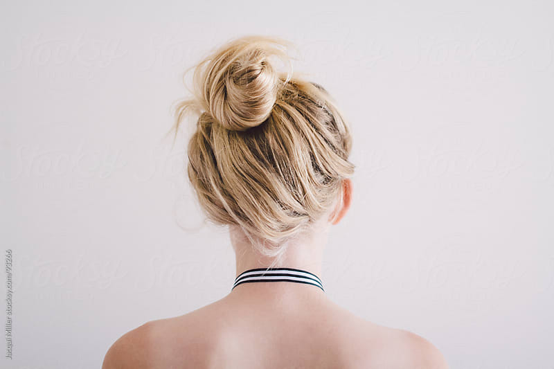 Girl with a messy topknot by Jacqui Miller for Stocksy United
