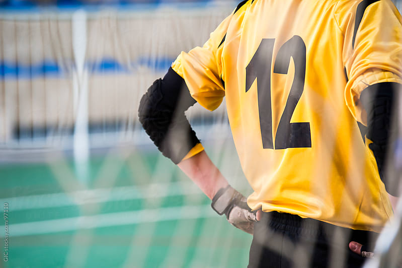 Soccer goalkeeper number 12 behind the net - Stock Image by GIC for Stocksy United