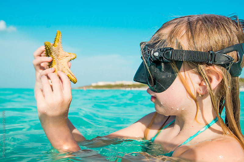 Little Girl Holding A Starfish Swimming Snorkeling at All Inclusive Caribbean Resort White Sand Beach by JP Danko for Stocksy United
