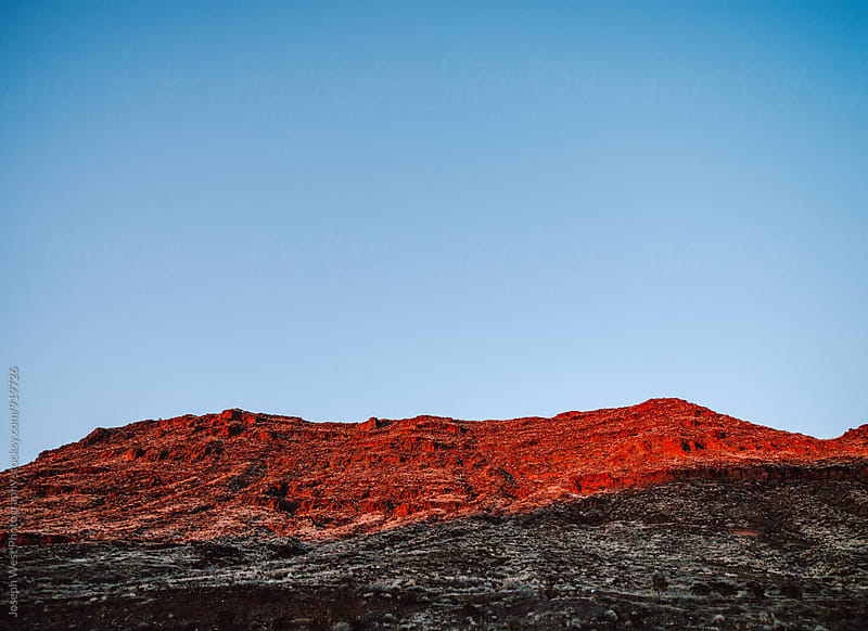 Rocky red hill in the desert by Joseph West Photography for Stocksy United