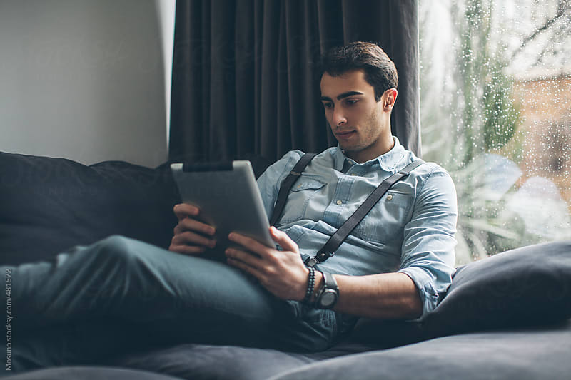 Man Using Tablet Computer at Home by Mosuno for Stocksy United