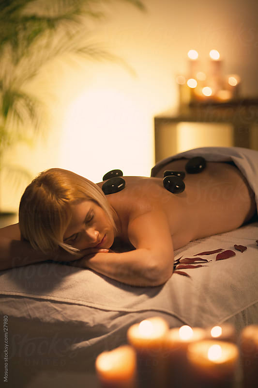 Woman enjoying hot stones treatment. by Mosuno for Stocksy United
