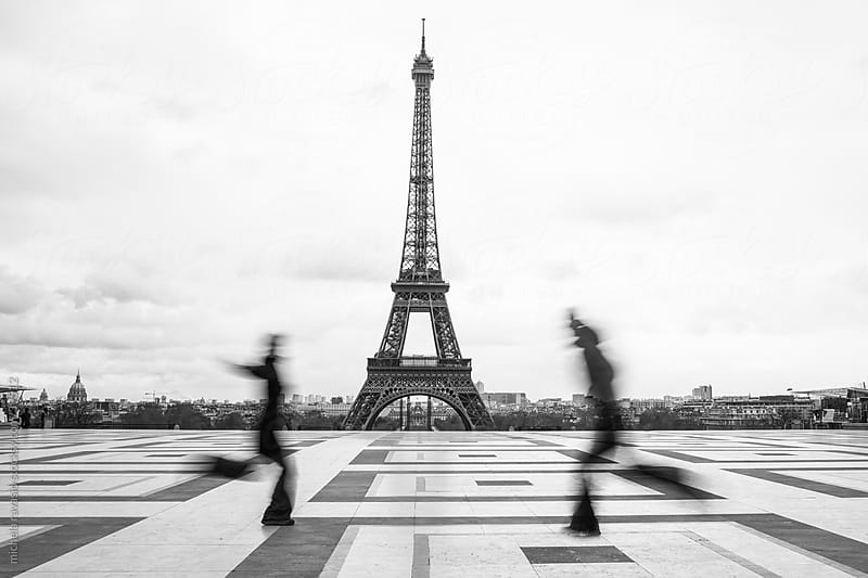 Two people run to embrace with the Eiffel Tower in the background by michela ravasio for Stocksy United