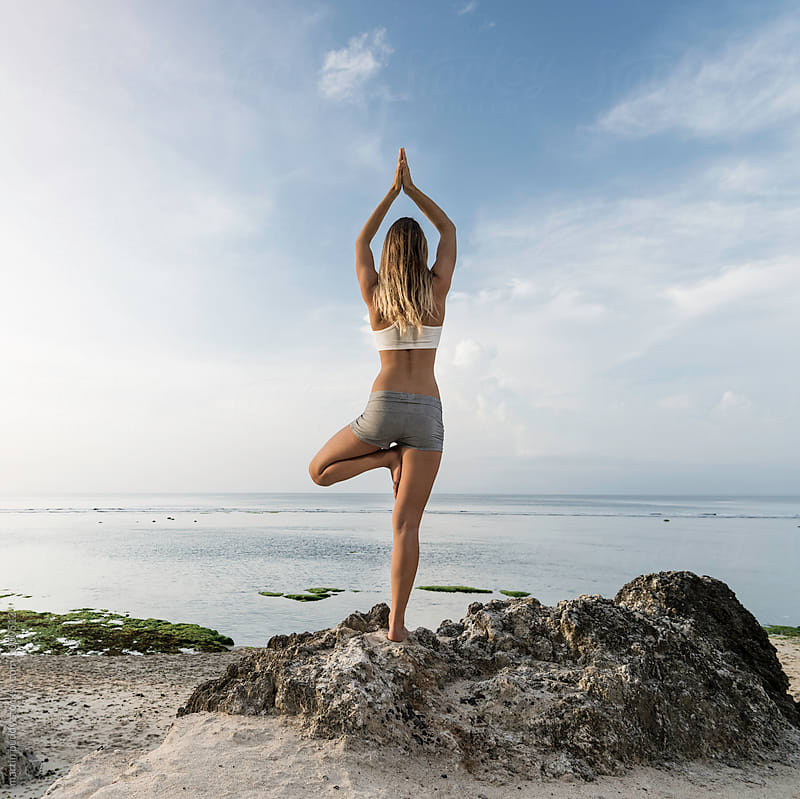 young woman practicing yoga on beach by martin puddy for Stocksy United