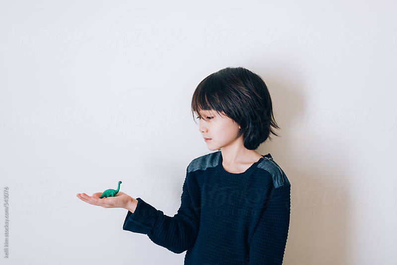 young mixed race boy plays alone with his dinosaur by kelli kim for Stocksy United