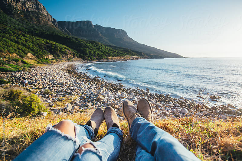 Point of view of a couples feet relaxing whilst overlooking a scenic rocky beach by Micky Wiswedel for Stocksy United