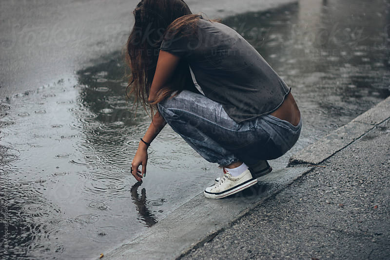 Young woman in the rain by Maja Topcagic for Stocksy United