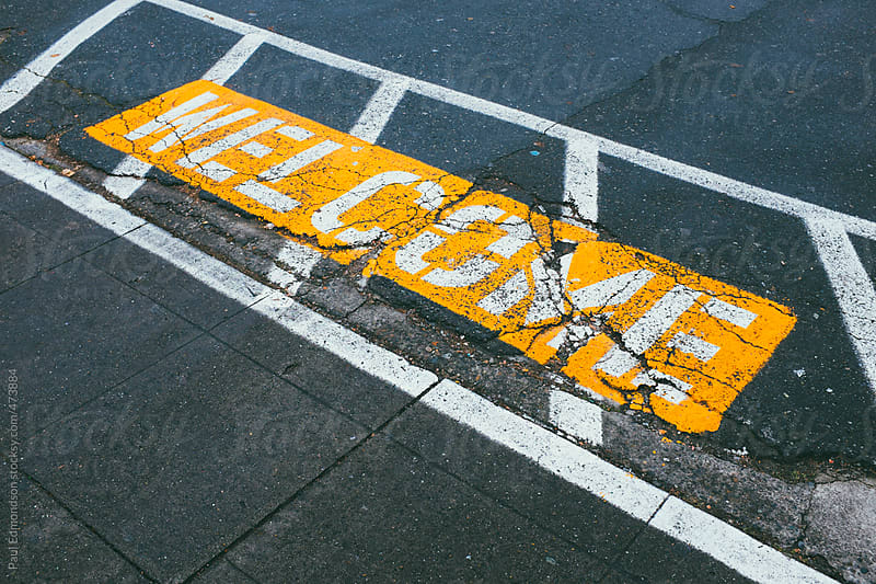 The word WELCOME painted on urban street by Paul Edmondson for Stocksy United