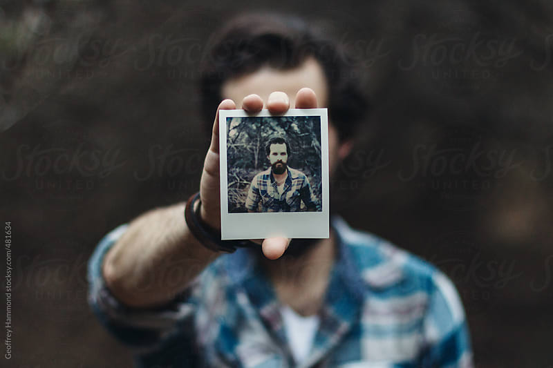Man Holding Polaroid Portrait of Self in Forest by Geoffrey Hammond for Stocksy United