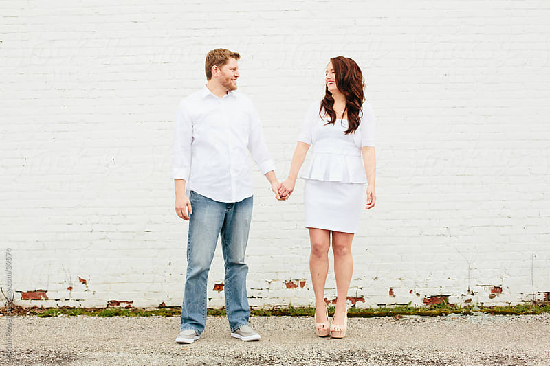 white couple holding hands by Brian Powell for Stocksy United