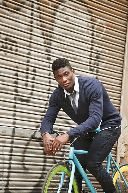 African young man riding a bicycle outdoors. by BONNINSTUDIO for Stocksy United
