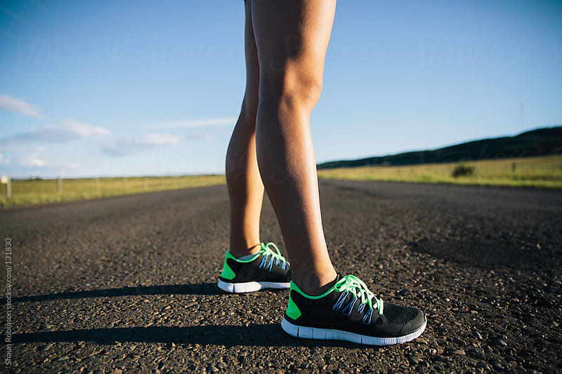 runners legs on country road by Shaun Robinson for Stocksy United