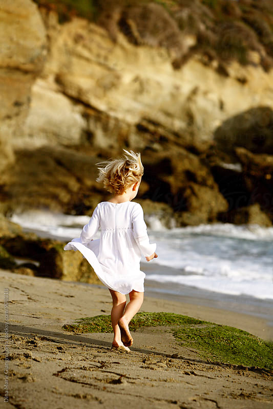 Little Girl Running on Beach With Dress and Hair in Motion by Dina Giangregorio for Stocksy United