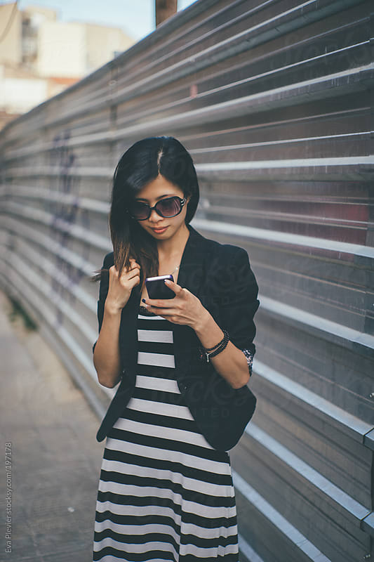 Girl texting on her mobile phone. by Eva Plevier for Stocksy United