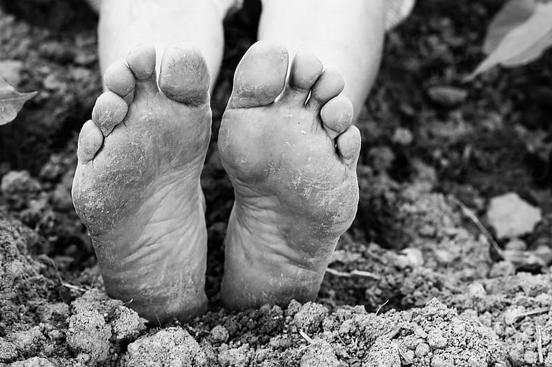 Worn dirty feet in soil by J Danielle Wehunt for Stocksy United