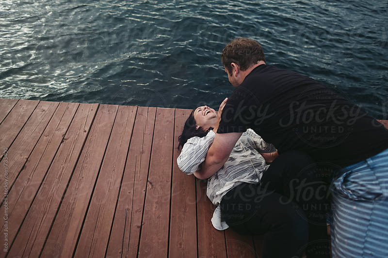 Young playful couple lying together on dock at lake by Rob and Julia Campbell for Stocksy United