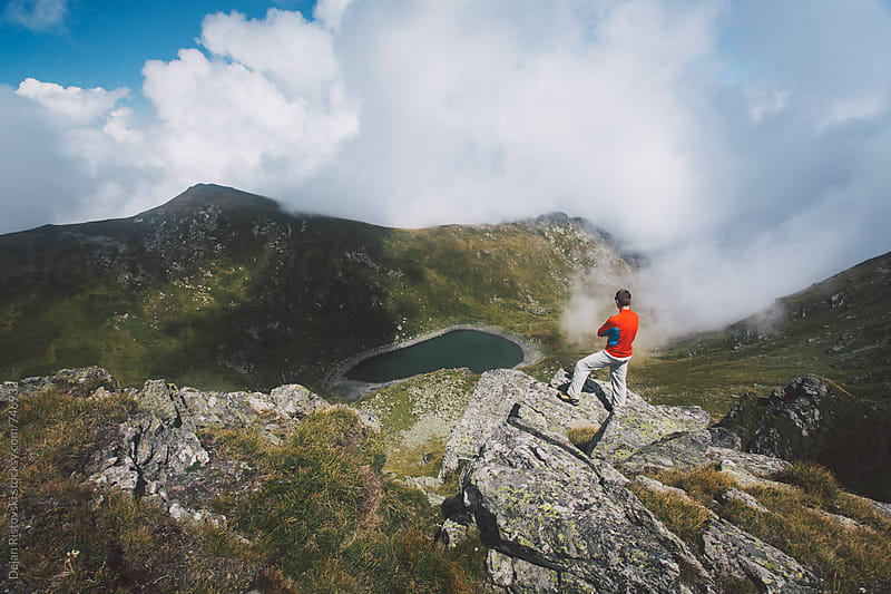 Man standing on a cliff and watching the view by Dejan Ristovski for Stocksy United