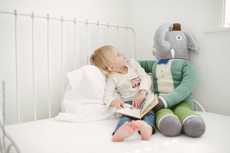 Cute young toddler looking a large elephant doll with book by Kristin Rogers Photography for Stocksy United