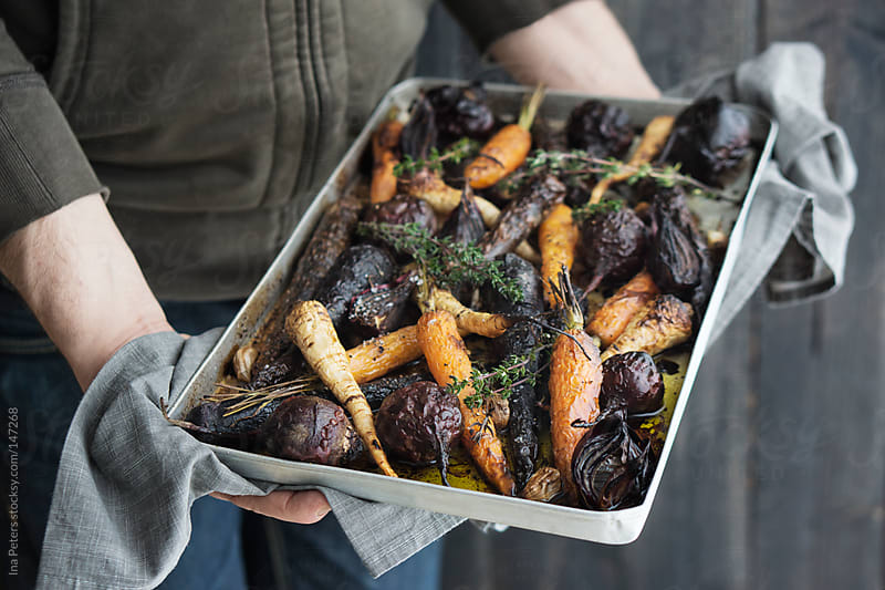 Food: Man holding a Bakig Tray with Grilled Root Vegetables by Ina Peters for Stocksy United