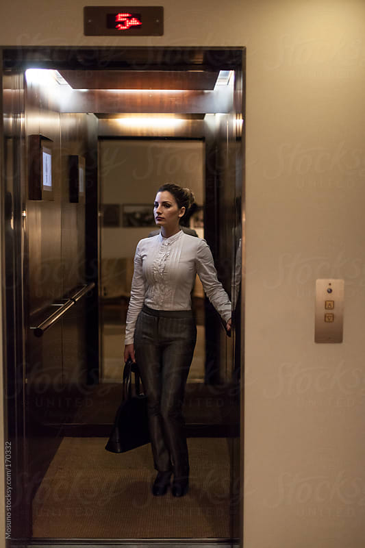 Businesswoman Standing in a Hotel Elevator by Mosuno for Stocksy United