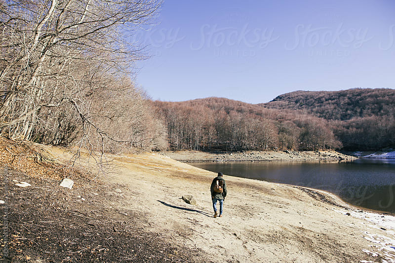 Mountaineer walking near lake on a sunny winter day. by BONNINSTUDIO for Stocksy United