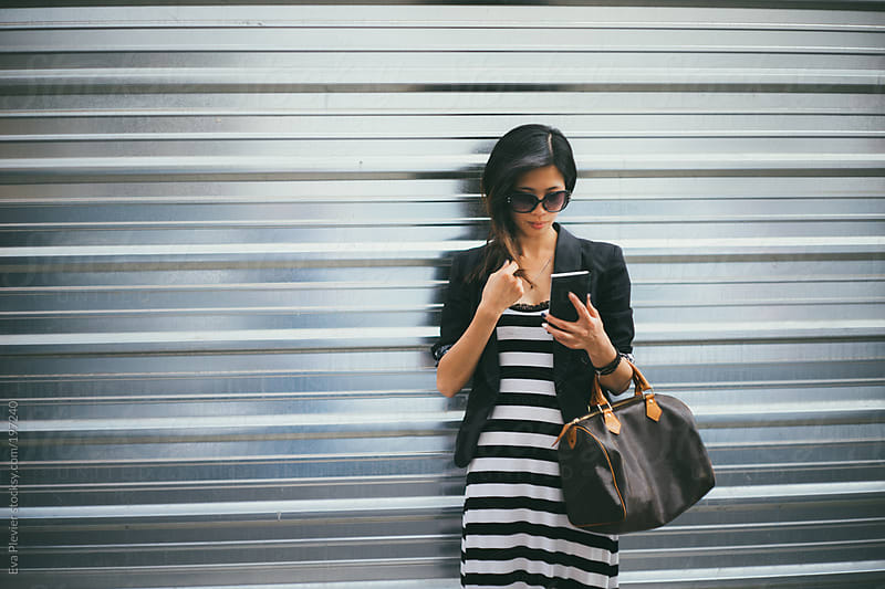 Asian girl texting on her mobile phone. by Eva Plevier for Stocksy United