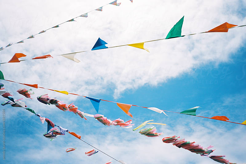 bright colored flags against blue sky on film by wendy laurel for Stocksy United