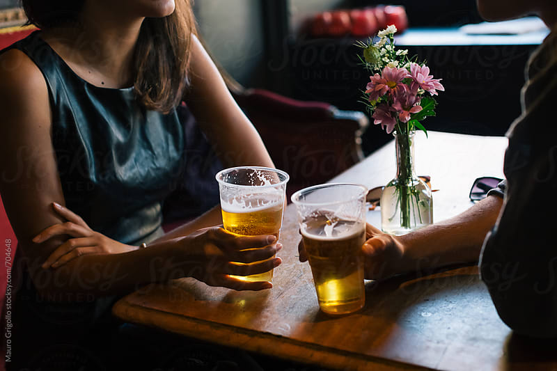 Couple drinking a beer in a Pub by Mauro Grigollo for Stocksy United