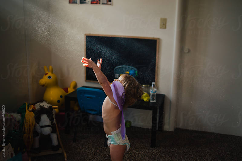 Toddler girl reaching for light beams by Jessica Byrum for Stocksy United