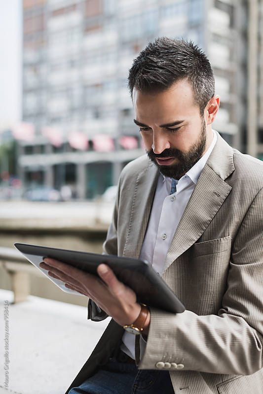 Businessman using digital tablet outdoor. by Mauro Grigollo for Stocksy United