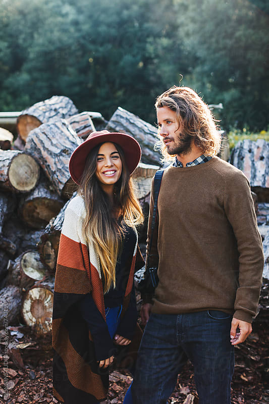 Portrait of a hipster couple standing in front of a stack of trunks. by BONNINSTUDIO for Stocksy United
