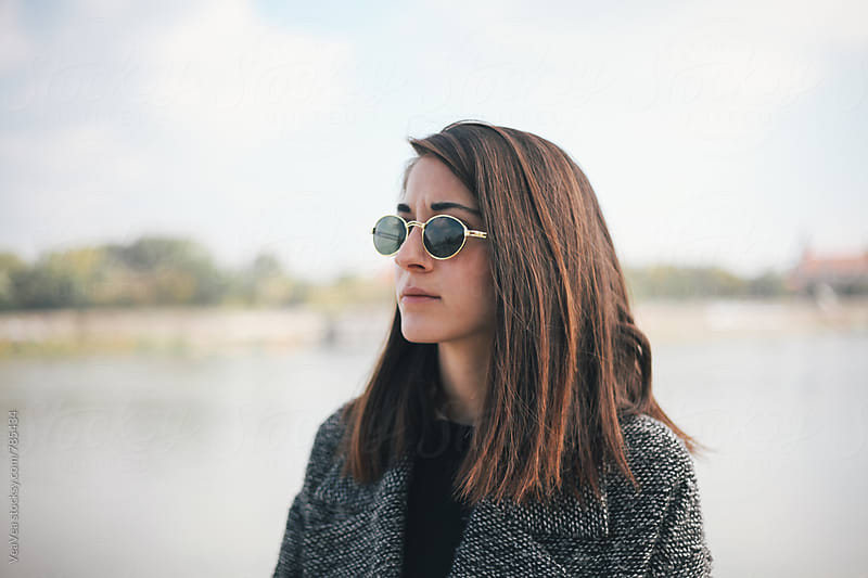 Portrait of a young woman with sunglasses outdoors by VeaVea for Stocksy United