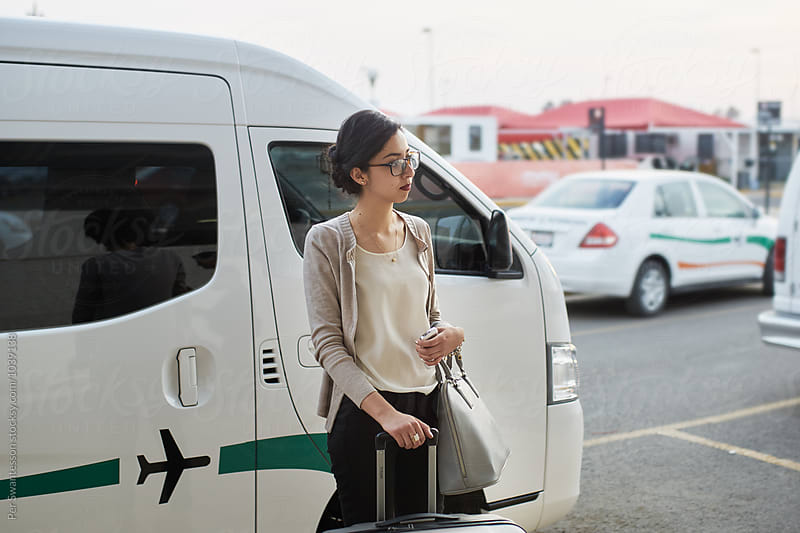 Young woman waiting for transportation outside airport pick up area